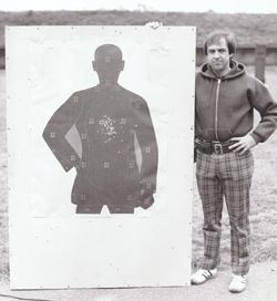 Black and white photo of a man standing next to a target.